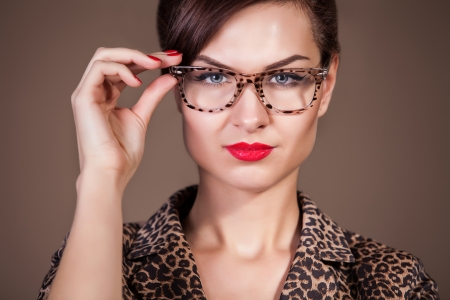 Close-up portrait of attractive caucasian woman in glasses on brown background photo