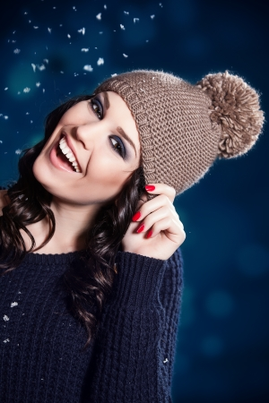 Portrait of sensual woman enjoying snow. Wearing warm hat photo