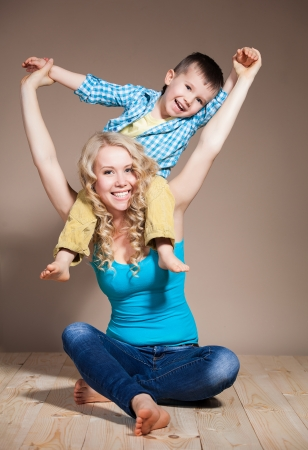 Portrait of a young mother and small son having fun. Family, adorable kid, love and happiness concept photo