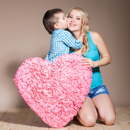 Portrait of a young woman with her son while holding a heart shape sign photo