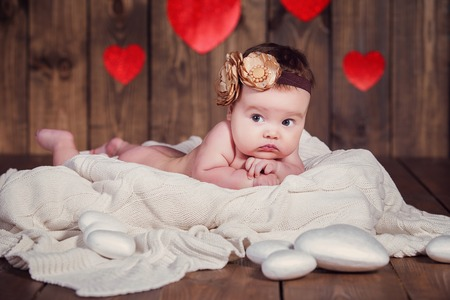 Sweet little baby girl crawling on a wooden floor photo