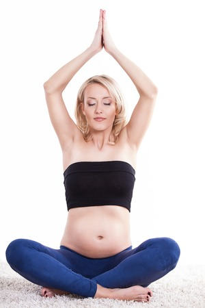 A pregnant young woman performing a yoga routine to relax over white background photo