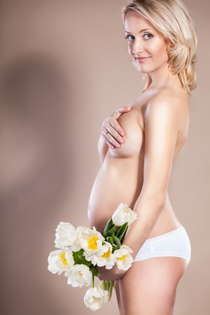 A bare pregnant woman holding a bouquet of flowers photo