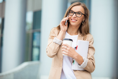 Successful businesswoman talking on cellphone while walking outdoor. City business woman working. photo