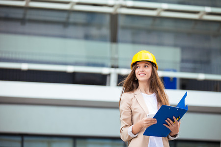 A pretty young woman working as architect on a construction site Stock Photo