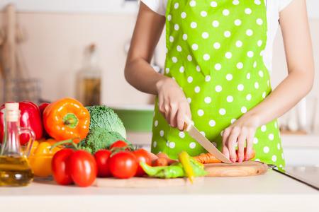 Human hands cooking vegetables salad in kitchen