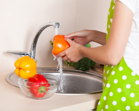 woman washing vegetables at kitchen photo
