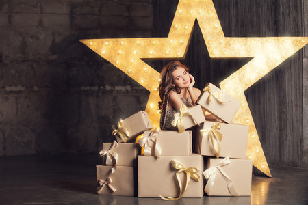 Fashion woman with lots of gifts. Brodway star on background
