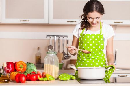 cuchillo de cocina: Mujer joven que cocina en la cocina. Alimentaci�n saludable. Concepto de dieta. Estilo de vida saludable. Cocinar en casa. Preparar Alimentos Foto de archivo