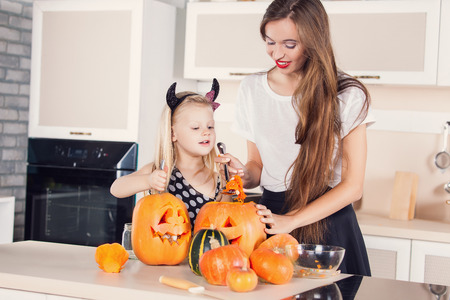 Kid on Halloween party making carved pumpkin with a little help from her mother photo