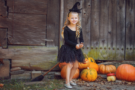 Shot of a little girl in halloween costume posing with pumpkins during Halloween party
