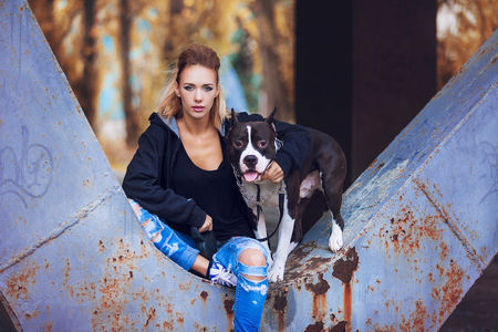 hot girl nude: modern punk fashion, portrait of a beautiful model posing on the street with dog. Modern Youth Lifestyle Concept Stock Photo