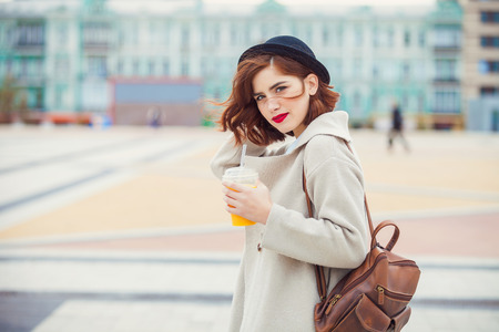 young stylish pretty woman with juice posing in the city streets. vacation europe