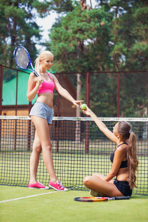 doubles: Beautiful female tennis players playing doubles at tennis at the tennis court