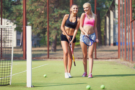 tenis: Tenistas femeninas hermosas juegan dobles en el tenis en la cancha de tenis