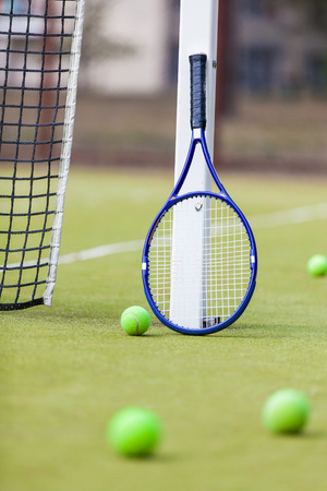 avocation: A tennis racquet and balls on a clay tennis court