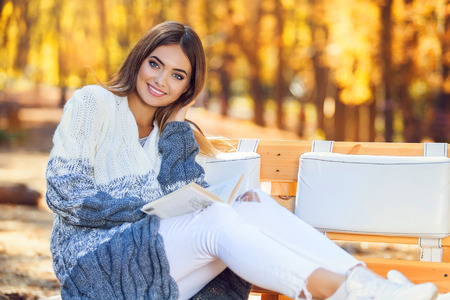 gorgeous: Gorgeous brunette woman reading a book in the autumn park