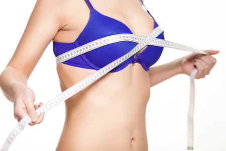 breast beauty: Young fit woman checking her breast measurement. Over white background Stock Photo