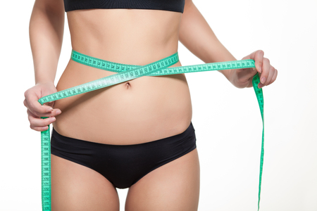waistline: Woman measuring her waistline with a green measuring tape, isolated in white. Perfect Slim Body. Diet