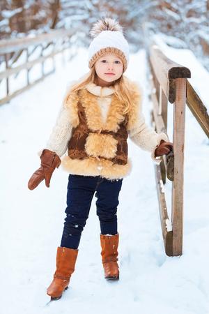 niño modelo: Niña que disfruta de un día jugando en el bosque de invierno