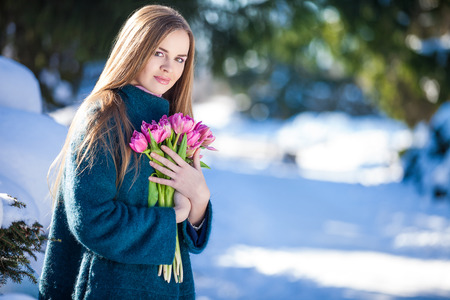 winter flower: Young woman with a bouquet of tulips at the park. Snow in early spring