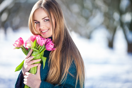 early spring snow: Young woman with a bouquet of tulips at the park. Snow in early spring