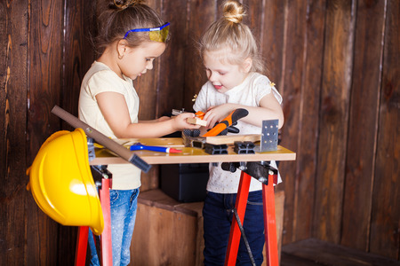 young worker: Two little girls making very interesting creations with tools and wood at home Stock Photo