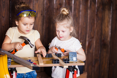 Two little girls making very interesting creations with tools and wood at home Standard-Bild