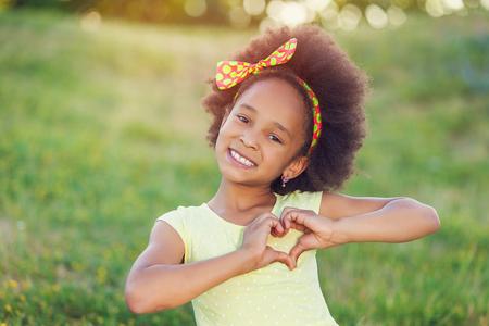 Открытый портрет довольно смешанной расы афро-американской девушки, улыбаясь на открытом воздухе