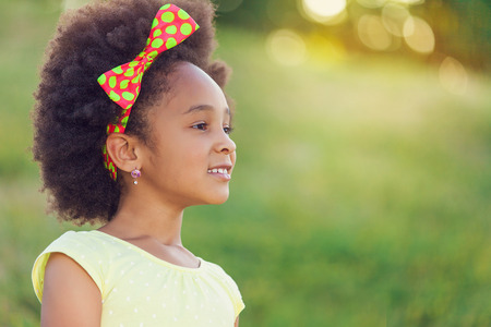 one little girl: Outdoor portrait of pretty mixed race African-American girl smiling outdoor