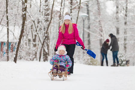 sledging people: Family walking in a winter park Stock Photo