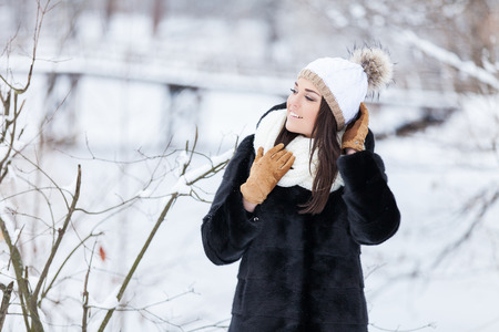 warm clothing: Winter woman in snow outside in nature. Portrait closeup outdoors in snow