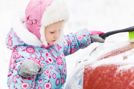 idling: Little Girl removing snow from car Stock Photo