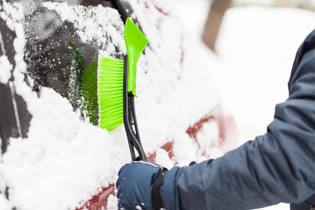 winter weather: Transportation, winter, weather, people and vehicle concept - man cleaning snow from car with brush Stock Photo
