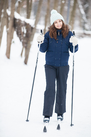 respite: Portrait of young woman with ski in winter time