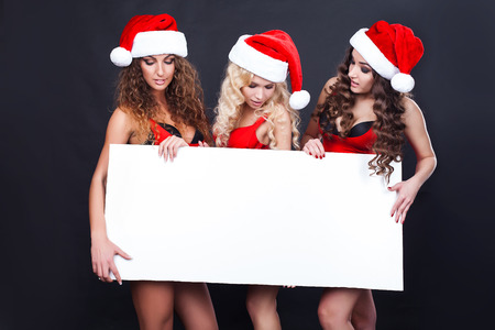 Group of cheerful santa girls hold the blank placard with copy text. Christmas greetings card