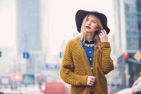 winter day: Fashionable young woman posing outside in a city street. Winter Fashion Stock Photo