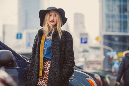 Fashionable young woman posing outside in a city street. Winter Fashion Imagens