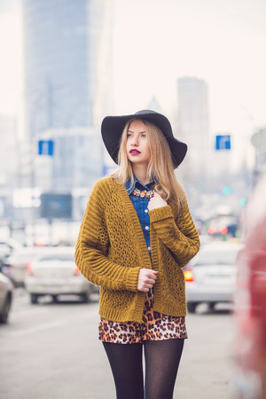 Fashionable young woman posing outside in a city street. Winter Fashion Stock Photo