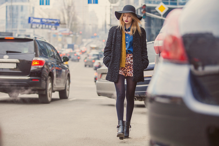 urban style: Fashionable young woman posing outside in a city street. Winter Fashion Stock Photo