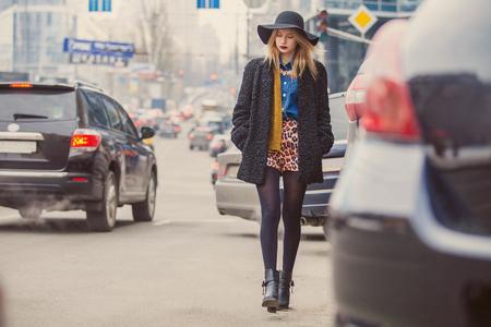 estilo urbano: Mujer joven de moda que presenta afuera en una calle de la ciudad. Moda de Invierno