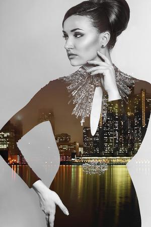superimposed: Composite image of a elegant young woman superimposed on an image of a city at night. Double exposure Stock Photo