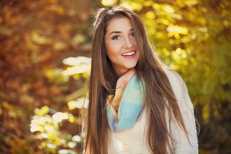 blissful: Excited happy woman smiling joyful and blissful holding autumn leaves outside in colorful fall forest Stock Photo