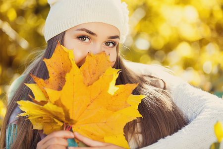 fall beauty: Excited happy woman smiling joyful and blissful holding autumn leaves outside in colorful fall forest Stock Photo