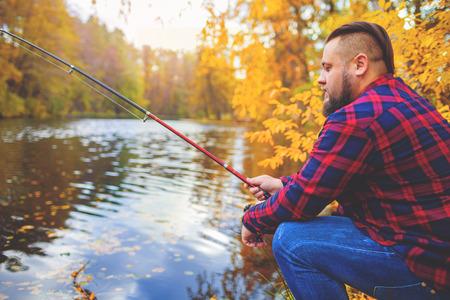 pescador: Joven pescador pesca con vara barba. R�o en el fondo Foto de archivo