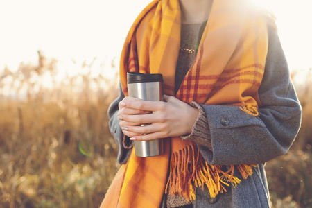 fall winter: Romantic girl with thermo cup in a field in sunset light.