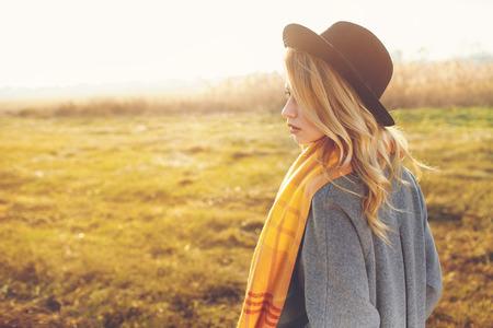 Portret van romantische meisje in een veld in zonsondergang licht. Stockfoto