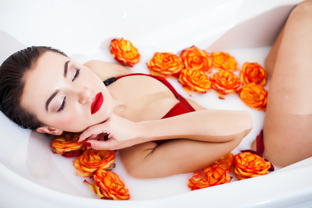 enjoys: Attractive girl enjoys a bath with milk and roses Stock Photo