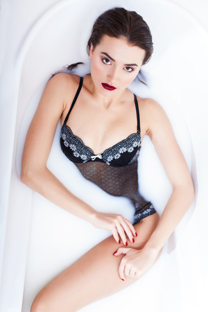 enjoys: Attractive girl dressed lingerie enjoys a bath with milk Stock Photo