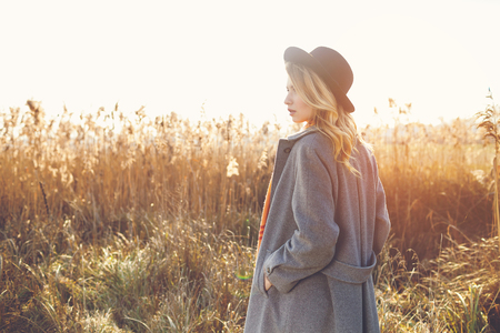 Romantic girl walking in a field in sunset light. Stock Photo